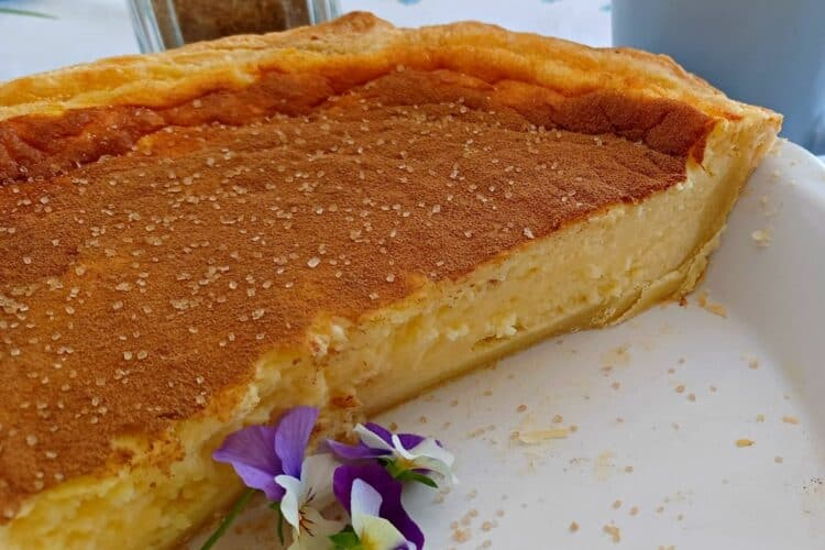 Baked Milk tart, a traditional South African dessert, is a smooth and creamy custard filling baked in a sweet pastry crust.